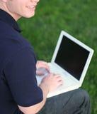 Lächeln, grünes Gras und Laptop lizenzfreie stockfotografie
