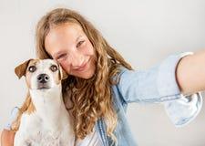 Lächeln jugendlich mit dem Hund, der selfie Foto auf Smartphone über nettem Mädchen des weißen Hintergrundes macht stockfoto