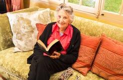 Lächeln lesend ältere, grau-haarige Frau, in ihrem Wohnzimmer, lizenzfreies stockfoto
