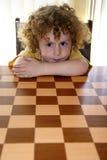 Lächeln-lockiger Junge u. Schach Lizenzfreie Stockfotografie