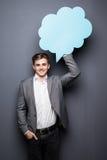 Lächeln-Mann, der blaue leere Spracheblase mit Raum für Text auf grauem Hintergrund hält Stockbilder