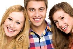Lächeln mit drei jungen Leuten Stockbild