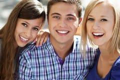Lächeln mit drei jungen Leuten Stockbilder