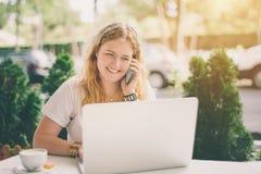 Lächeln plus Größenmodellmädchen mit Laptop und Smartphone Stockfoto