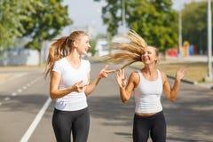 Lächeln, Positiv, hübsche Mädchen, die auf einem Parkhintergrund laufen Sport mit Freundkonzept lizenzfreie stockfotografie
