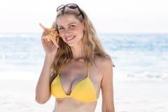 Lächeln recht blond im Bikini, der einen Starfish hält und Betrachten der Kamera Stockfotografie
