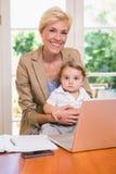 Lächeln recht blond mit seinem Sohn, der Laptop verwendet Lizenzfreie Stockfotos