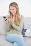 Lächeln recht blonde Versenden von SMS-Nachrichten beim Sitzen auf angenehmem Sofa Lizenzfreie Stockfotos