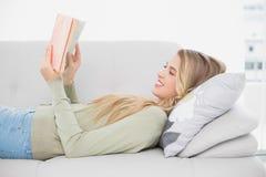 Lächeln recht blondes Lesebuch, das auf angenehmem Sofa liegt Lizenzfreies Stockfoto