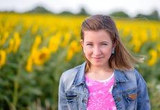 Lächeln recht blondes Mädchen gegen Sonnenblumenfeld Lizenzfreie Stockbilder