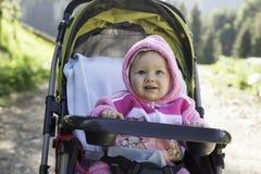 Lächeln recht kleines Kindermädchen im Buggy stockfotos