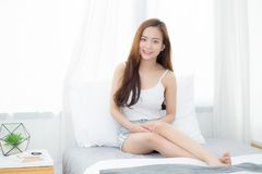 Lächeln schönes junges asiatisches Frauensitzen des Porträts und das Fenster am Schlafzimmer, während mit Sonnenaufgang am Morgen stockfotografie