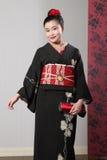 Lächeln Sie von der asiatischen Frau im schwarzen japanischen Kimono Lizenzfreie Stockfotografie