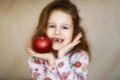 Lächeln und Griffe eines süßes kleines gelocktes zahnlos Mädchens in ihren Händen ein roter Apfel, ein Porträt eines glücklichen  lizenzfreie stockfotografie