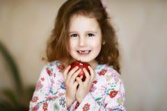 Lächeln und Griffe eines süßes kleines gelocktes zahnlos Mädchens in ihren Palmen ein roter Apfel, der Milchzähne verloren hat stockbild