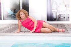 Lächeln und recht blonde mittlere Greisin legend auf Poolplattform Lizenzfreie Stockbilder