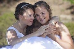 Lächeln und Umarmung mit zwei Bräuten in den Naturumgebungen Lizenzfreies Stockfoto