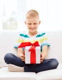 Lächeln wenig haltene Geschenkbox, die auf Couch sitzt Stockfotografie