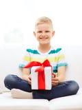 Lächeln wenig haltene Geschenkbox, die auf Couch sitzt Lizenzfreie Stockbilder