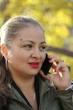 Lächelnd, spricht nettes Mädchen am Telefon draußen Stockbild