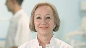 Lächelnde ältere Ärztin, die Kamera betrachtet Stockfoto