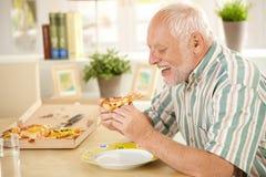 Lächelnde ältere Fleisch fressende Pizzascheibe Lizenzfreies Stockbild