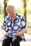 Lächelnde ältere Frau auf der Bank Lizenzfreie Stockfotografie