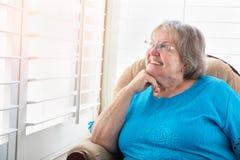 Lächelnde ältere Frau, die aus ihrem Fenster heraus anstarrt Stockbilder