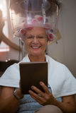 Lächelnde ältere Frau, die digitale Tablette beim Sitzen unter Haardampfer verwendet Lizenzfreies Stockfoto