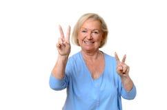 Lächelnde ältere Frau, die ein doppeltes Vzeichen gibt Stockbild