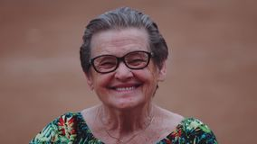 Lächelnde ältere Frau, die Kamera betrachtet stock footage