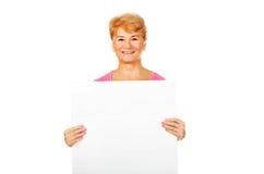 Lächelnde ältere Frau, die leere Fahne hält Lizenzfreie Stockfotos