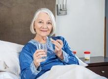 Lächelnde ältere Frau, die Medizin an der Krankenpflege einnimmt stockbilder