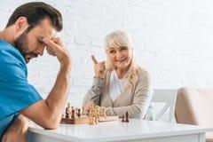 lächelnde ältere Frau, die mit dem Finger zeigt und nachher umgekippten Mann betrachtet stockfoto