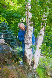 Lächelnde ältere Frau hinter der Birke Stockfotografie