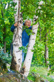 Lächelnde ältere Frau hinter der Birke Stockbilder