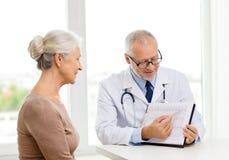 Lächelnde ältere Frau und Doktorsitzung Stockbild