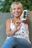 Lächelnde ältere Frau zeigt ihr intelligentes Telefon Stockfotos