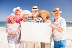 Lächelnde ältere Freunde, die leeres Papier halten Stockfotos