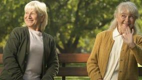 Lächelnde ältere Hände wellenartig bewegende und draußen flirtende Damen, sitzende Bank, Sympathie stock footage