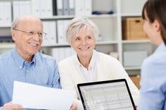 Lächelnde ältere Paarsitzung mit einem Vermittler lizenzfreie stockbilder