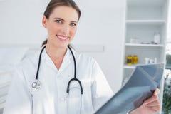Lächelnde Ärztin, die eine Radiographie durchlöchert Stockfotografie