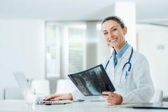 Lächelnde Ärztin, die einen Röntgenstrahl überprüft stockbilder