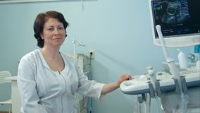 Lächelnde Ärztin, die nahe bei Ultraschalldiagnosegerät sitzt Stockbild