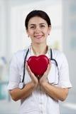 Lächelnde Ärztin, die rotes Herz und stethascope hält Lizenzfreie Stockbilder