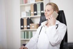 Lächelnde Ärztin, die um Handy ersucht Lizenzfreie Stockbilder