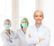 Lächelnde Ärztin mit Gruppe Medizinern Lizenzfreies Stockfoto