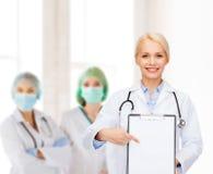 Lächelnde Ärztin mit Klemmbrett Stockbilder
