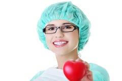 Lächelnde Ärztin oder Krankenschwester, die rotes Herz halten Lizenzfreie Stockbilder