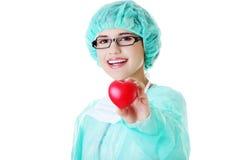 Lächelnde Ärztin oder Krankenschwester, die rotes Herz halten Lizenzfreie Stockfotos